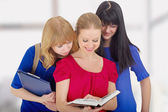 Three nice girls college discussing the book — Stockfoto