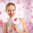 Beautiful girl reads a postcard valentine — Stock Photo #8520641