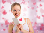 Beautiful girl reads a postcard valentine — Stock Photo