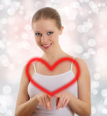 Beautiful young woman draws a big red heart — Stock Photo