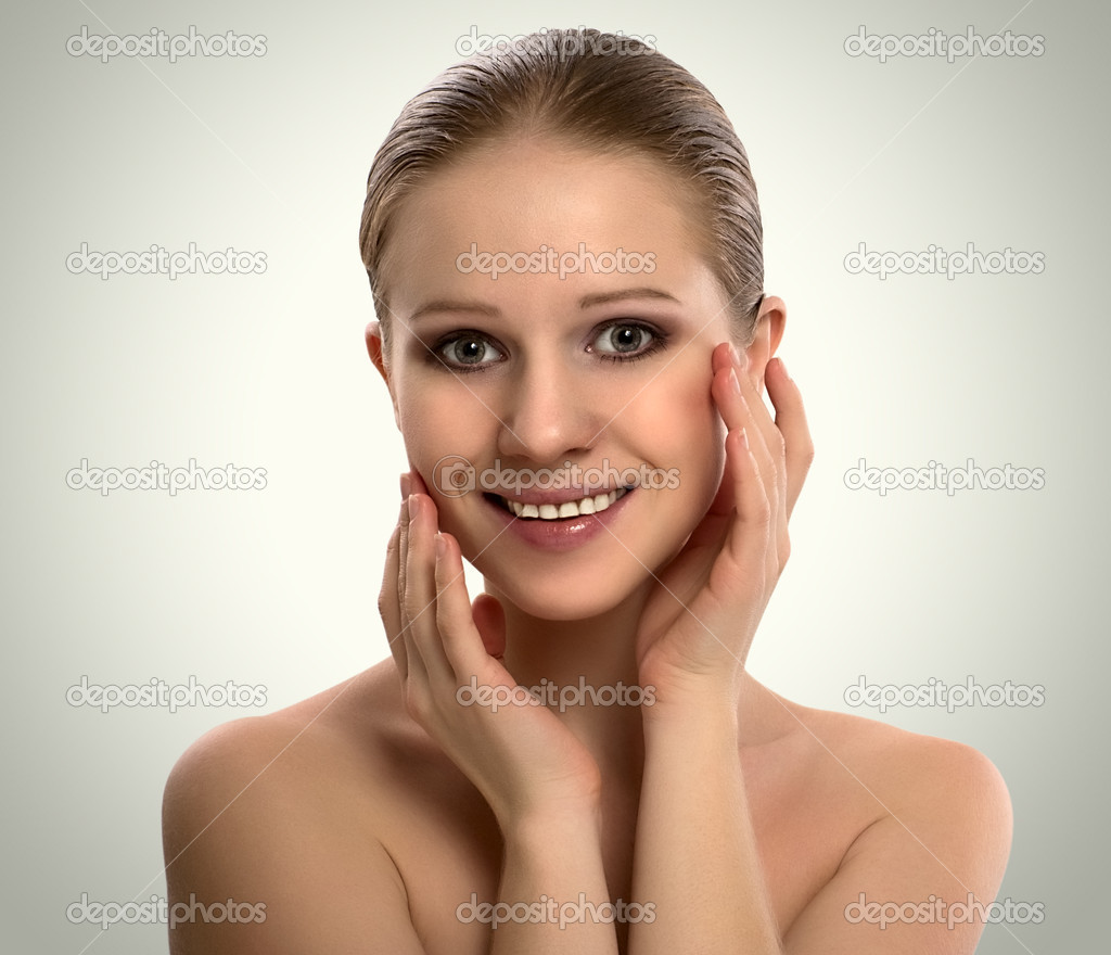 Beautiful young woman cares for the skin on a gray background — Stock Photo #8912063