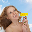Stock Photo: Beautiful girl with flowing hair with yellow gerberflower ag