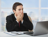 Surprised frightened businessman looking at a laptop, his han — Stock Photo