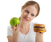 Attractive young woman makes a choice between healthy and unheal — Stock Photo