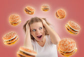 Diet concept. young woman is under stress, burgers are flying ar — Stock Photo