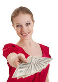 Beautiful cheerful girl in a red blouse holds out a wad of money — Stock Photo