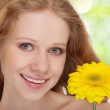 Young beautiful blonde woman with a yellow gerbera flower close — Stock Photo