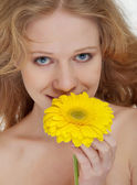 Beautiful blonde girl with a yellow gerbera flower — Stock Photo