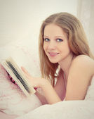 Young beautiful blonde woman reading a book while lying in bed — Stock Photo