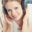 Beautiful smiling girl enjoys listening to music on headphones o — Stock Photo #9611214