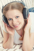 Beautiful smiling girl enjoys listening to music on headphones o — Stock Photo