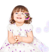 Little girl catches the bubbles — Stock Photo