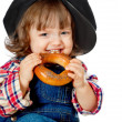 A beautiful little baby in a cap eating a loaf of bread — Stock Photo