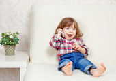 Beautiful little child holds a cell phone — Stock Photo