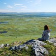 Woman against the green tableland with many small lakes. - Stock Photo