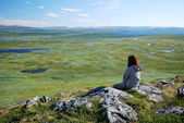 Woman against the green tableland with many small lakes. — Stock Photo