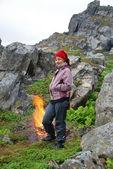 Tourist near the bonfire under the rock — Stock Photo