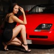 Pretty woman near the red car — Stock Photo