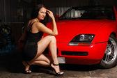 Pretty woman near the red car — Stock Photo