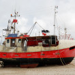 Fishing boat on the sand coast. — Stock Photo