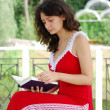 Stock Photo: Young womreading book in park.