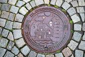 Sewer manhole on stone pavement of Trondheim. — Stock Photo