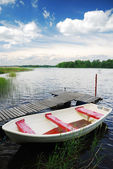 шведское озеро с небольшой деревянный причал и лодка — Стоковое фото