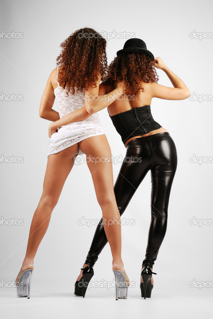 Two go-go are standing back and hugging. Her legs are planted apart on high stiletto heels. The young women are twins. One of them is wearing black leather leggings and top. The other sister is wearing a white transparent dress. — Stock Photo #10451676