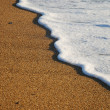 Close-up of sand beach with the foamy wave - Stock Photo