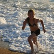 Happy girl running away from the breaking waves. - Stock Photo