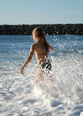 Young girl playing in the breaking waves. — Stock Photo