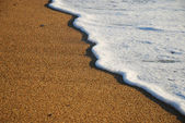 Close-up of sand beach with the foamy wave — Stock Photo