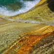 Close-up of multicolored rocks under clear water flowing. - Stock Photo