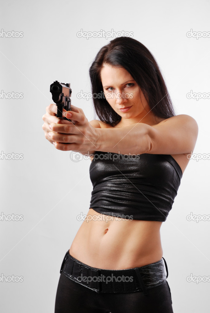 Serious woman is aiming a handgun at close range. She is looking at the camera. Pretty girl is wearing a black leather top and tight pants. — Stock Photo #9000935