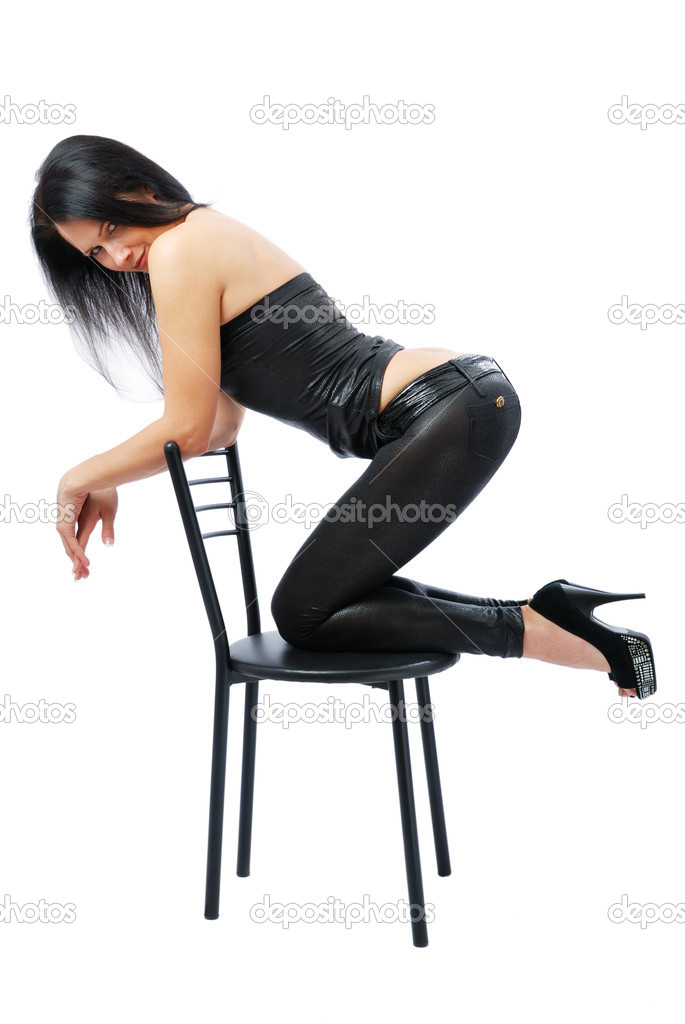 Sexy woman kneels on the black chair sideways. She is looking at the camera. Pretty girl is wearing a black leather top, tight pants and high-heeled shoes. — Stock Photo #9643665