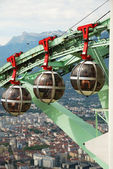Grenoble is a large city at the foot of the French Alps. Les Bulles are the egg-shaped cable cars carrying tourists over the city. — Stock Photo