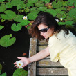 Woman near the lake with water lilies. — Stock Photo