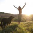 Beautiful young woman raises her arms to the sun whilst walking her dog — Stock Photo #10373071