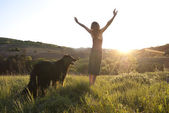 Beautiful young woman raises her arms to the sun whilst walking her dog — Stock Photo