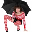 Woman with umbrella crouching — Stock Photo