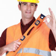 Man with spirit-level giving the ok sign - Stock Photo