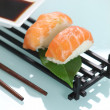 Raw salmon sat on ball of boiled rice -  