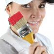 Woman holding a paintbrush - Stock Photo
