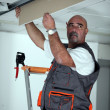 Manual worker repairing ceiling panel - Stock Photo