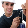 Portrait of young bricklayer installing bell - Stock Photo