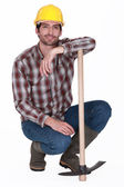Handsome bricklayer with arm resting on pickaxe — Stock Photo