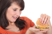 Brunette looking at burger — Stock Photo