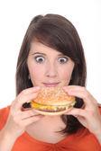 Brunette girl attacked Burger — Stock Photo