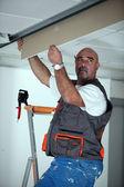 Manual worker repairing ceiling panel — Stock Photo