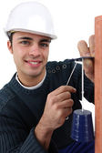 Portrait of young bricklayer installing bell — Stock Photo